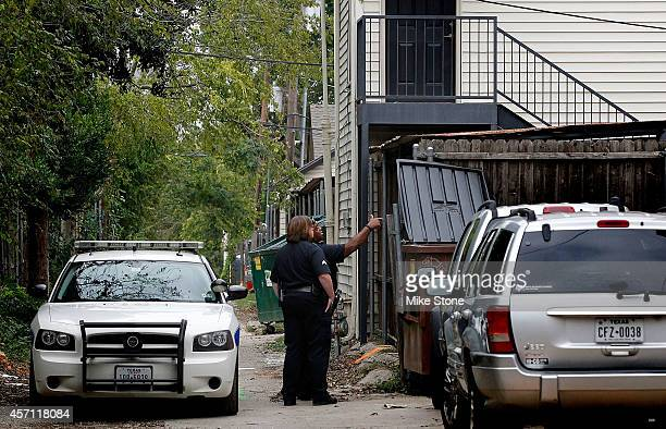 Police officers inspect an alley behind the apartment where a second person diagnosed with the Ebola virus resides on October 12 2014 in Dallas Texas...