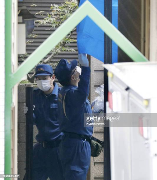 Police officers inspect an apartment complex in Zama Kanagawa Prefecture on Oct 31 where nine dismembered bodies were found in an apartment earlier...
