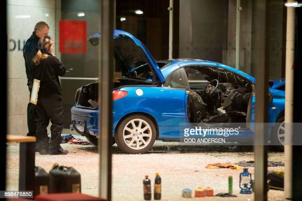 TOPSHOT Police officers inspect damage in the lobby of the German Social Democratic Party headquarters after a car was used to ram the building in...