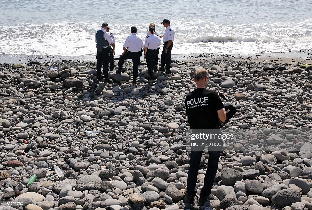 Police officers inspect metallic debris found on a beach in Saint-Denis on the French Reunion Island in the Indian Ocean on August 2, 2015, close to where a Boeing 777 wing part believed to belong to missing flight MH370 washed up last week. A piece of metal was found on La Reunion island, where a Boeing 777 wing part believed to belong to missing flight MH370 washed up last week, said a source close to the investigation. Investigators on the Indian Ocean island took the debris into evidence as part of their probe into the fate of Malaysia Airlines flight MH370, however nothing indicated the piece of metal came from an airplane, the source said.