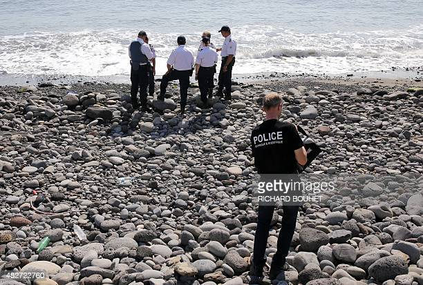 Police officers inspect metallic debris found on a beach in Saint-Denis on the French Reunion Island in the Indian Ocean on August 2 close to where a...