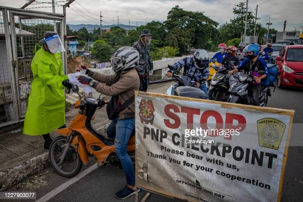 Police officers inspect motorists at a quarantine checkpoint on the first day of a reimposed lockdown to curb the spread of COVID-19, on August 4,...