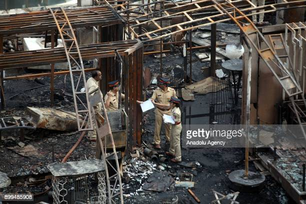 Police officers inspect the burning building after a fire broke out at a rooftop restaurant in Mumbai India on December 29 2017 At least 15 people...