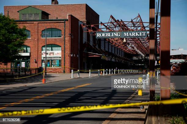 Police officers inspect the crime scene at the Roebling Market on June 17 the morning after a shooting at an allnight art festival injured 20 people...