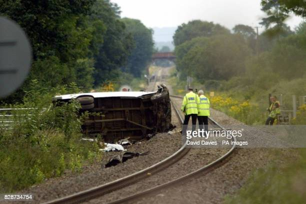 Police officers inspect the minibus which was in collision with a train on a unmanned level crossing two miles west of Evesham Worcestershire * Three...
