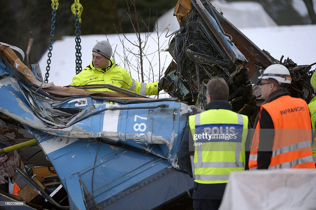 Police officers inspect the remains of a derailed train in Saltsjoebaden, near Stockholm, Sweden on January 28, 2013. The train crashed into a residential building on January 18, 2013 after a cleaning lady most likely set it in motion by accident.