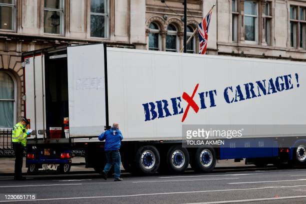 Police officers inspect the truck of a driver working in the shellfish industry who brought his truck to central London to protest against...