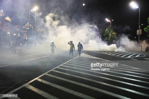 Police officers intervene in protesters with tear gas during a protest against new measures to curb the spread of the novel coronavirus in Belgrade...