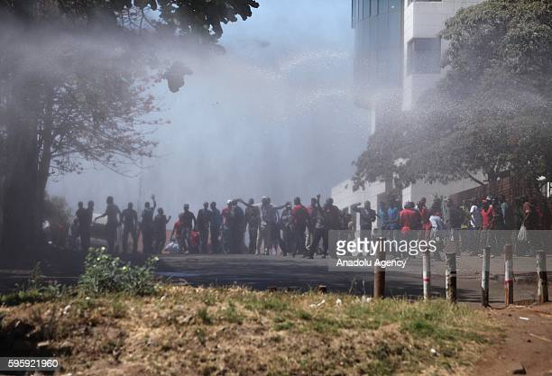 Police officers intervene to protesters during a protest against President of Zimbabwe Robert Mugabe and his government in Harare Zimbabwe on August...