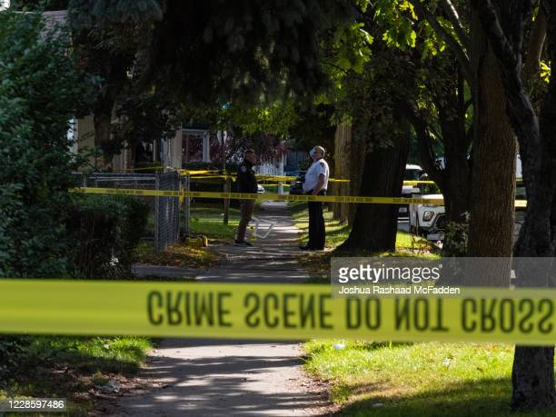 Police officers investigate a crime scene after a shooting at a backyard party on September 19 Rochester New York Two young adults a man and a woman...
