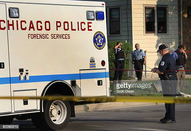 Police officers investigate a double homicide in the Kelvyn Park neighborhood July 28 2008 in Chicago Illinois Two men inside a car were shot and...