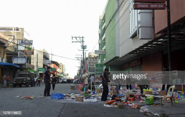 Police officers investigate at the site of an explosion outside a shopping mall in Cotabato City on the southern island of Mindanao on December 31...