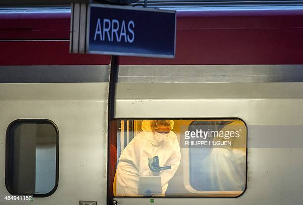 Police officers investigate on the crime scene inside a Thalys train of French national railway operator SNCF at the main train station in Arras...