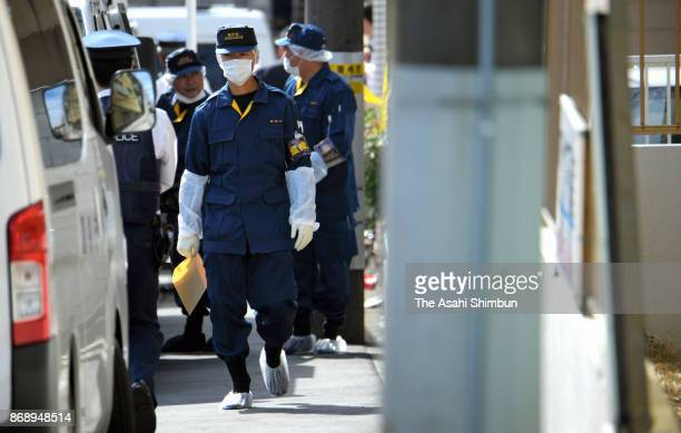 1 Police officers investigate the apartment where the body parts of nine people were found on November 1 2017 in Zama Kanagawa Japan Shiraishi...