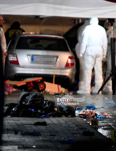 Police officers investigate the car of the man who drove into a carnival procession on February 24 2020 in Volkmarsen near Kassel central Germany...