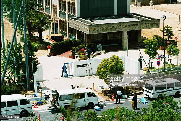 Police officers investigate the gate of a juniro high school where the severed head of the children was found on May 27 1997 in Kobe Hyogo Japan...