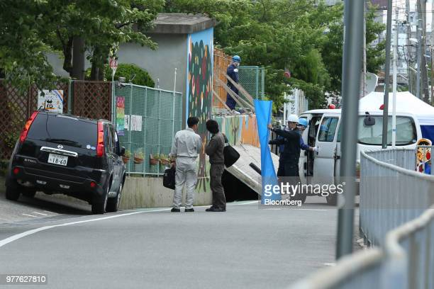 Police officers investigate the site where an elementary school student was killed after the walls next to the school pool had collapsed due to a...