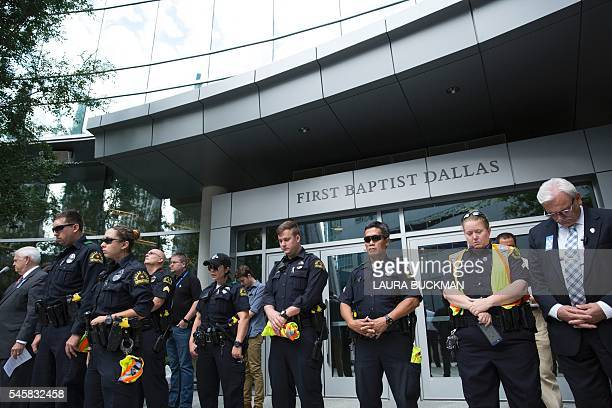 Police officers join parishioners of First Baptist Church in Dallas Texas as they gather on July 10 to pray for victims after 25yearold black army...