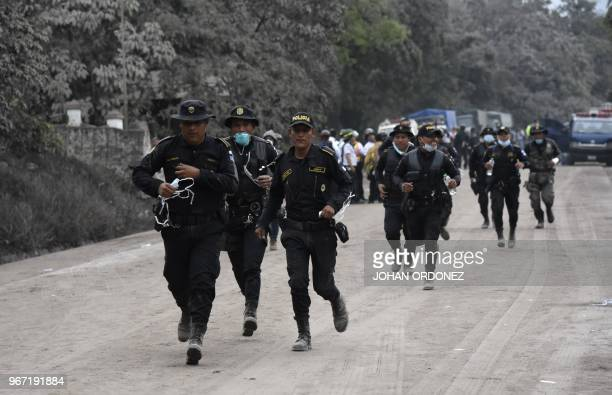 Police officers joining the search for victims run in San Miguel Los Lotes a village in Escuintla Department about 35 km southwest of Guatemala City...