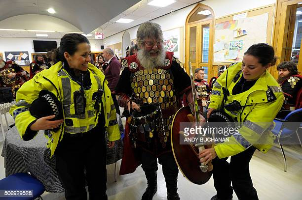 Police officers joke with a participant dressed as a Viking as they get breakfast in a cafe before the annual Up Helly Aa festival in Lerwick...