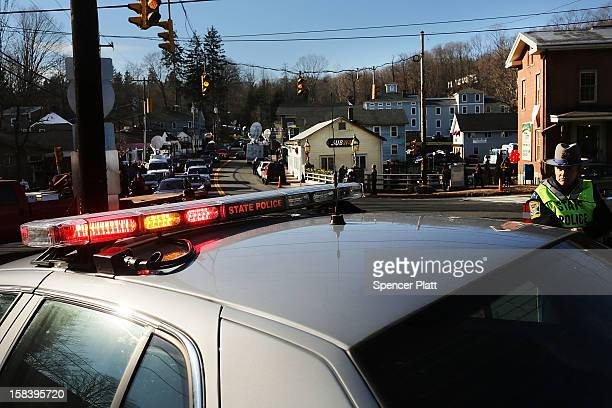 Police officers keep guard at the entrance to the street leading to the Sandy Hook School on December 15 2012 in Newtown Connecticut Twenty six...