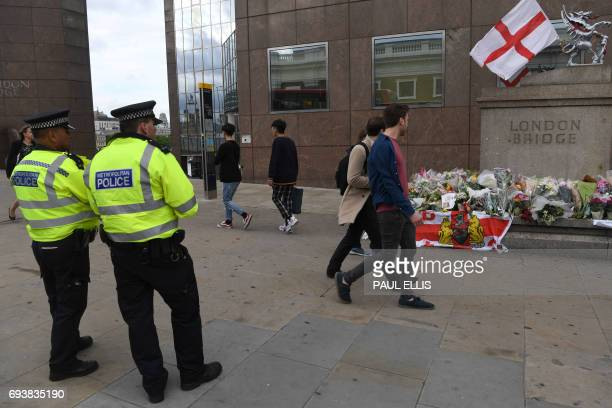 Police officers keep watch as commuters walk past bouquets of flowers at the southern end of London Bridge in London on June 8 2017 following the...