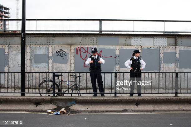 Police officers keep watch as revellers and paraders pack the streets of Notting Hill in west London for the main day of the 2018 Notting Hill...