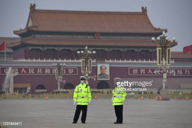 Police officers keep watch at Tiananmen Square ahead of the closing session of the National Peoples Congress in Beijing on March 11, 2021.