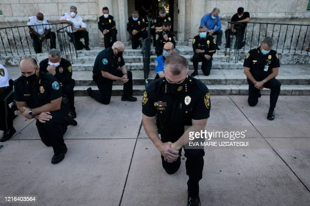 TOPSHOT Police officers kneel during a rally in Coral Gables Florida on May 30 2020 in response to the recent death of George Floyd an unarmed black...