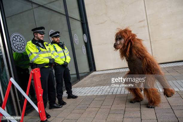 Police officers laugh as Greenpeace activists create a burnt smoldering rainforest with a lifelike animatronic orangutan at the headquarters of Oreo...