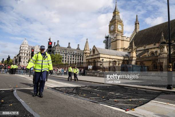 Police officers lay a new heavy goods vehicle tyre deflation system in the road before Judges process from Westminster Abbey to the Houses of...