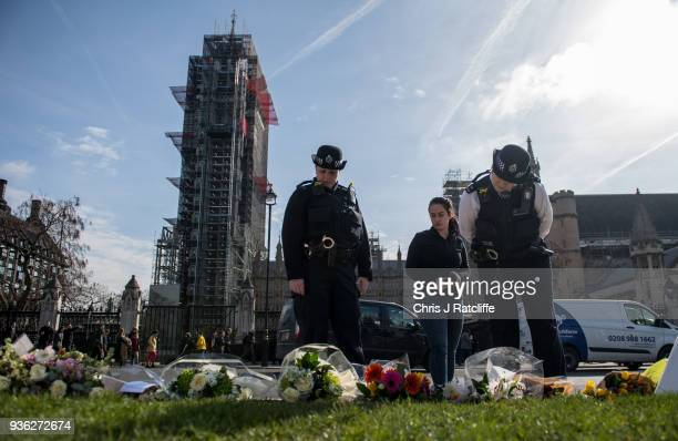 Police officers lay floral tributes in Parliament Square on the first anniversary of the Westminster Bridge terror attack on March 22 2018 in London...