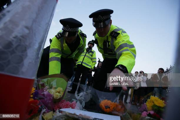 TOPSHOT Police officers lay flowers in honour of the victims of the March 22 terror attack at the end of Westminster Bridge by the Houses of...