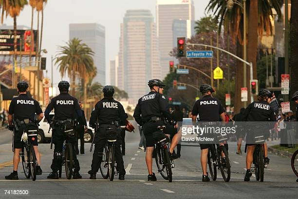 Police officers lead the way as protesters hold a march and rally denouncing the actions of Los Angeles riot police at a May Day immigrant rights...