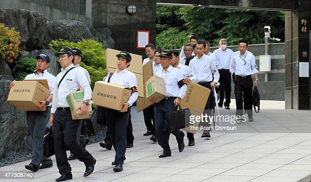 Police officers leave the home of Satoru Nomura head of the Kudokai crime syndicate after the raid on June 16 2015 in Kitakyushu Fukuoka Japan...