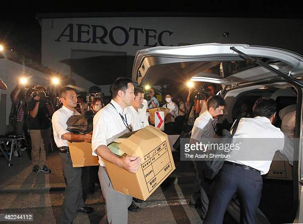 Police officers leave with boxes containing seized documents and stuffs after a raid at Nippon Aerotec on a light airplane crash on July 28, 2015 in...