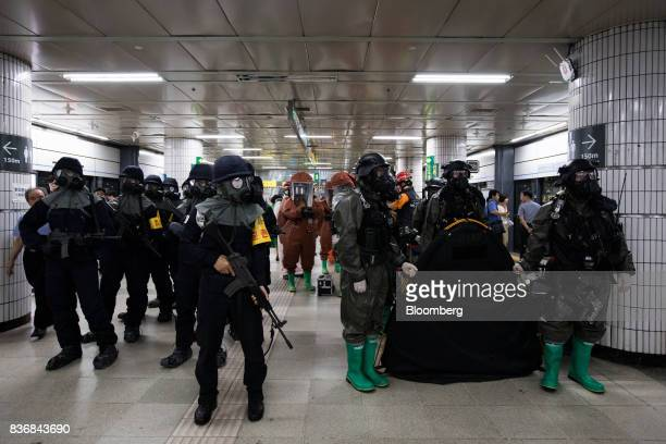 Police officers left and soldiers wearing gas masks participate in an antiterror drill on the sidelines of the Ulchi Freedom Guardian military...