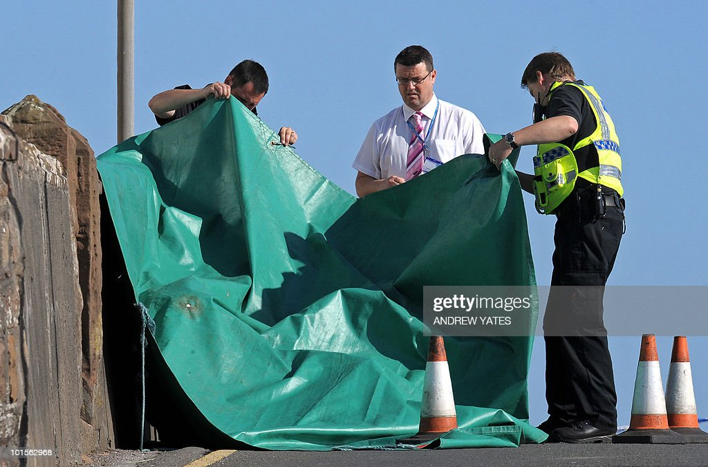 Police officers look a body at the scene of a shooting in Seascale, Cumbria, north west England on June 2, 2010. on June 2, 2010. A gunman killed at least 12 people after going on a rampage in a popular tourist area in northwest England on Wednesday, before apparently turning the gun on himself, police said. 'We can... confirm that from our current indications 12 people have lost their lives, plus Derrick Bird (the gunman),' said Deputy Chief Constable Stuart Hyde of the local police at a press conference.