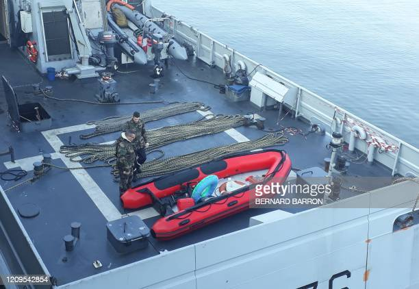Police officers look at an inflatable boat after they rescued 11 migrants in difficulty who tried to cross the Channel to Great Britain on April 09,...