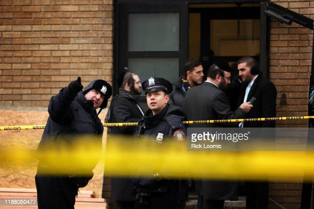 Police officers look at bullet holes in the windows of a school across the street from the JC Kosher Supermarket on December 11 2019 in Jersey City...