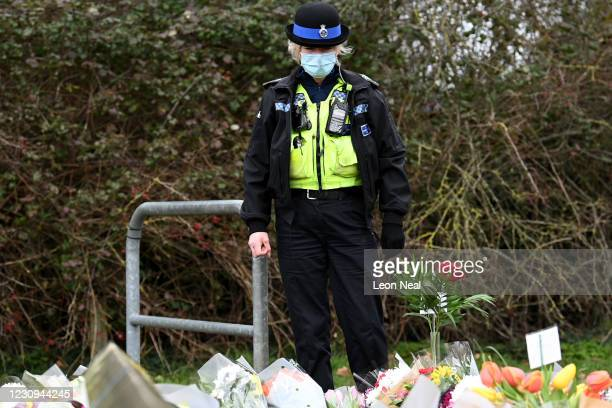 Police officers look at floral tributes laid near the former home of Captain Sir Tom Moore following the announcement of his death the previous day,...