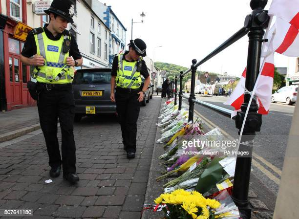 Police officers look at flowers left at the taxi rank in Whitehaven where Derrick Bird shot and killed a taxi driver as he went on a gun rampage...