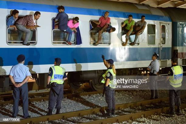 Police officers look at migrants sitting on the windows of a train at the railway station near the SlovenianCroatian border in Dobova Brezice on...