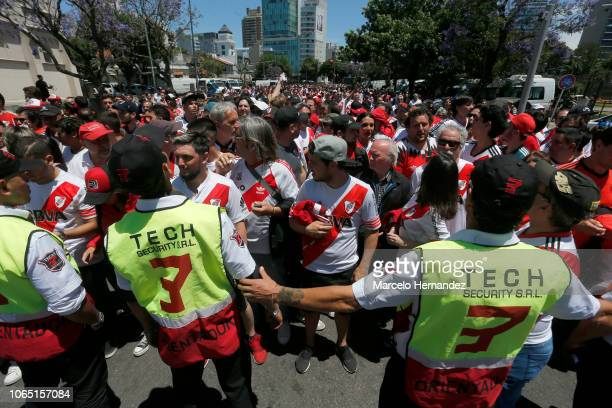 Police officers look at River fans on their way to the stadium prior the second leg of the final of Copa CONMEBOL Libertadores 2018 between River...