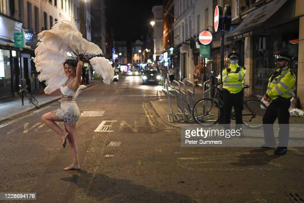 Police officers look on as an entertainer walks past in Soho on September 24 2020 in London England Pubs cafes and restaurants will have to shut at...