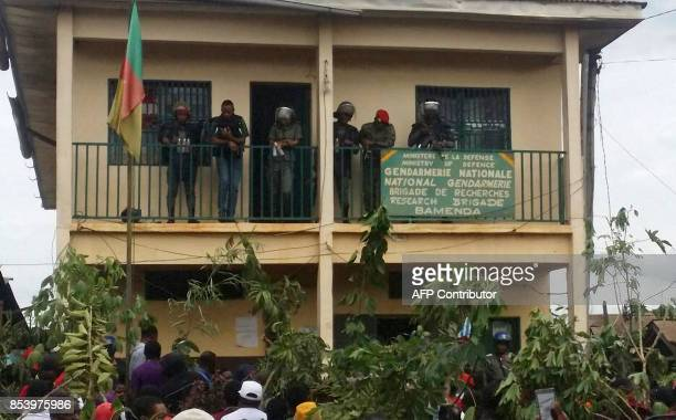Police officers look on as demonstrators gather outside of a police station during a protest against perceived discrimination in favour of the...