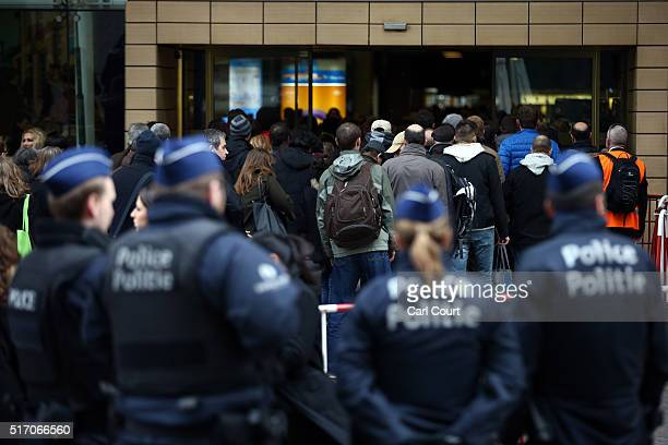 Police officers look on as people enter Brussels Midi train station on March 23 2016 in Brussels Belgium Belgium is observing three days of national...