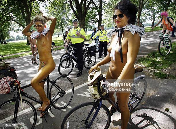 Police officers look on at two women painted gold as they prepare to set off on the 'World Naked Bike Ride' in Hyde Park in London on June 14 2008...