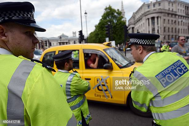 Police officers look on during a protest by London Black Cab drivers during a protest against a new private taxi service 'Uber' a mobile phone app in...