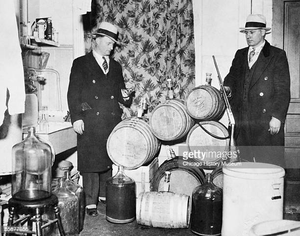 Police officers look over distilling equipment and guns confiscated during a Prohibition raid, Chicago, ca.1920s.